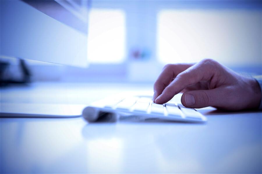 Männerhand auf Computertastatur